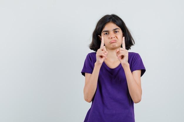 Petite fille pointant vers le haut en t-shirt et regardant abattu.