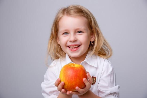 Petite fille à la pomme rouge sur blanc