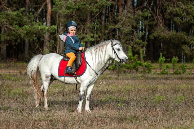 Petite fille sur un poney blanc dans la nature. jockey, hippodrome, équitation.