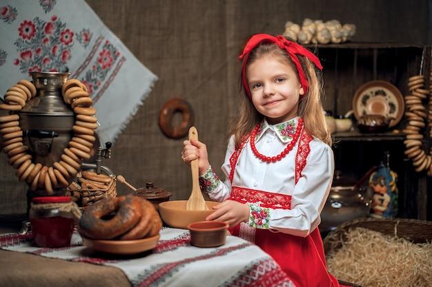 Petite fille portant un bandeau rouge et une chemise ornementale assis à table pleine de nourriture et de gros samovar célébrant maslenitsa