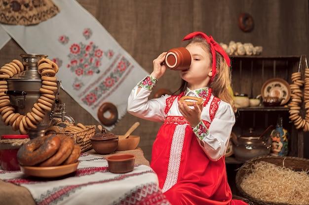 Petite fille portant un bandeau rouge et une chemise ornementale buvant du thé de samovar célébrant maslenitsa