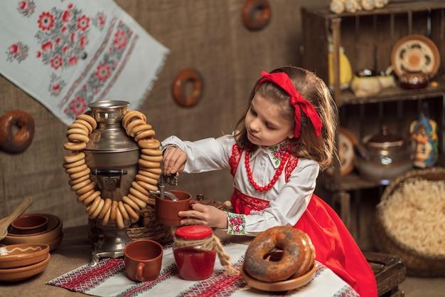 Petite fille portant un bandeau rouge et une chemise ornementale versant du thé de samovar célébrant maslenitsa