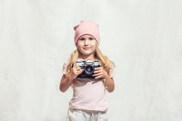 Petite fille portant un bennie rose tenant un appareil photo sur fond texturé blanc