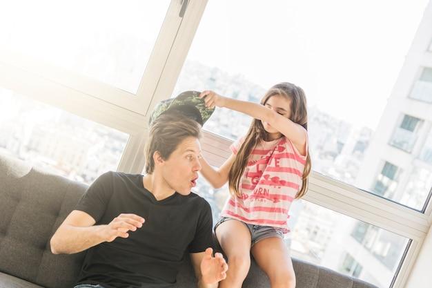 Petite fille portant une casquette à son père surpris sur le canapé