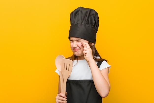 Petite fille portant un costume de chef croise les doigts pour avoir de la chance