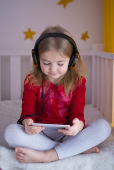 Petite fille, portant un écouteur en regardant le téléphone sur le lit de bébé