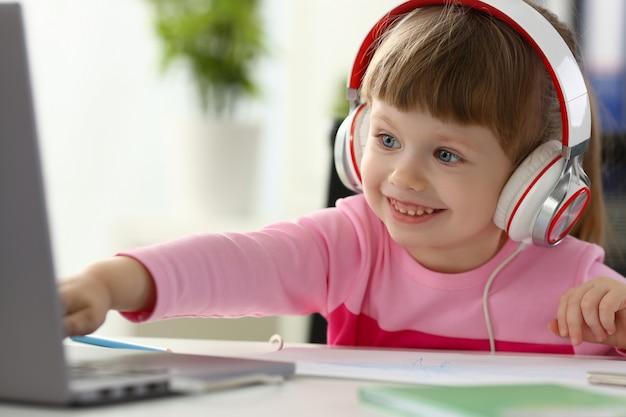 Petite fille portant des écouteurs utilise un ordinateur portable