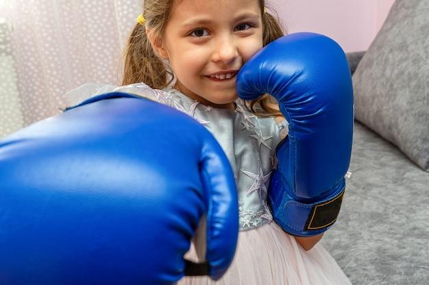 Petite fille portant des gants de boxe bleus et une robe de vacances avec des étoiles