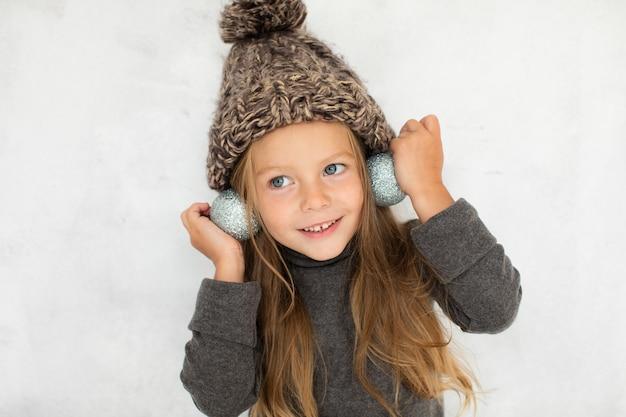 Petite fille portant des globes de noël comme boucles d'oreilles