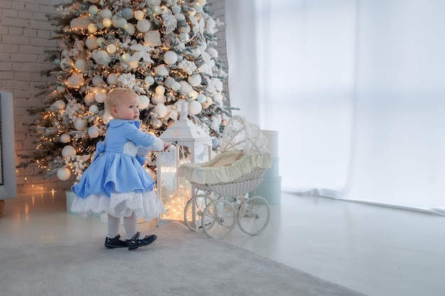 Une petite fille portant une jolie robe et un bandeau porte une poussette dans une pièce décorée de façon festive
