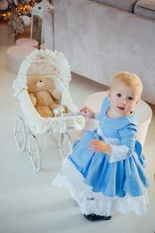 Une petite fille portant une jolie robe et un bandeau porte une poussette dans une pièce festive avec une guirlande