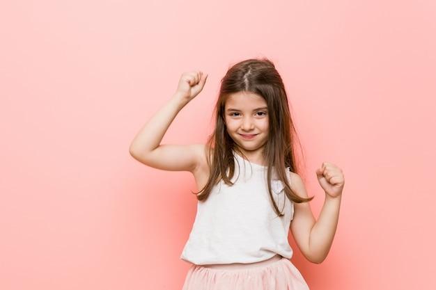 Petite fille portant un look princesse célébrant une journée spéciale, saute et lève les bras avec énergie.