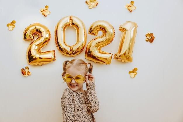 Petite fille portant des lunettes de mascarade en or souriant, s'amuser