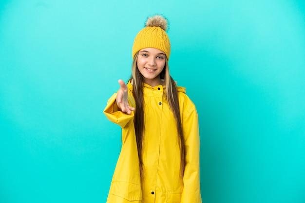 Petite fille portant un manteau imperméable sur fond bleu isolé se serrant la main pour conclure une bonne affaire