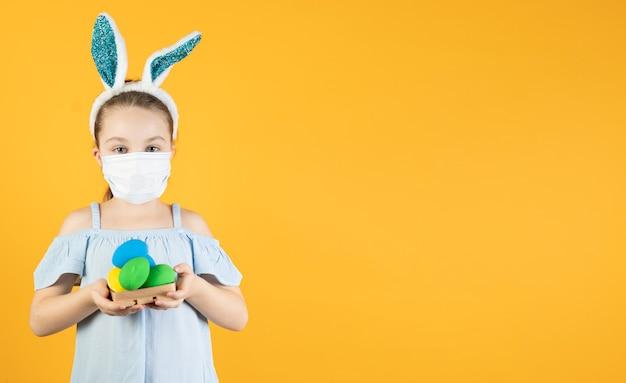 Une petite fille portant un masque médical de coronavirus sur son visage, sur sa tête avec des oreilles de lapin, tient des œufs de pâques de différentes couleurs dans ses mains