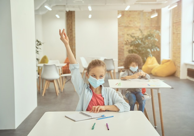 Une petite fille portant un masque protecteur pendant l'épidémie de coronavirus a levé la main en classe