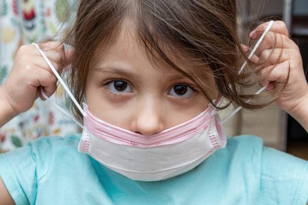 Petite fille portant un masque de protection médical à la maison pendant l'isolement en quarantaine