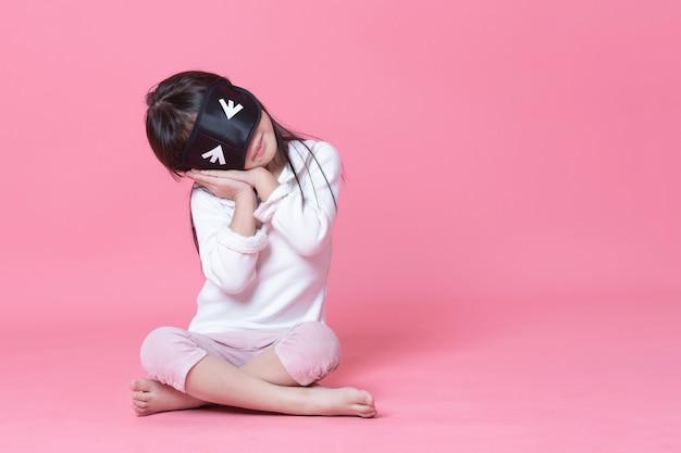 Petite fille portant un pyjama blanc et un masque noir assis dans une chambre rose au coucher.