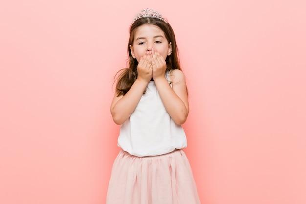 Petite fille portant un regard de princesse choqué couvrant la bouche avec les mains