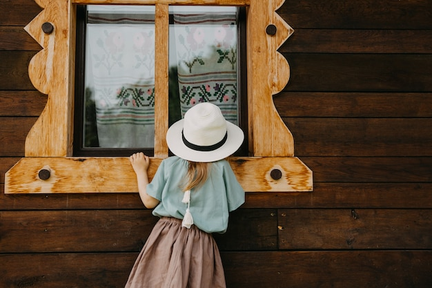 Petite fille portant une robe vintage, espionnage, regardant dans une vieille maison par la fenêtre