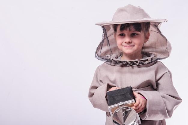 Une petite fille porte en costume d'abeille en studio fond blanc.
