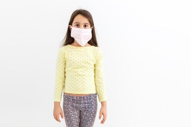 Petite fille porte un masque sur fond blanc, une fille portant un masque médical de protection covid-19 ou un coronavirus d'une personne infectée, protégée par la couronne aide à protéger pour le monde et les gens arrêtent l'avertissement de virus