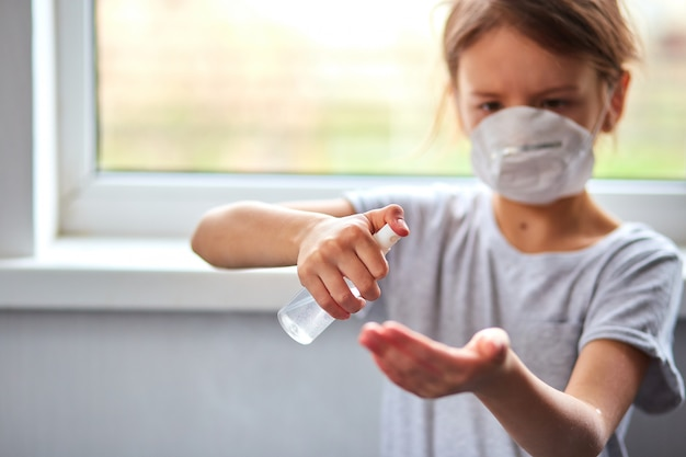 Petite fille porte un masque hygiénique et appuie sur un spray d'alcool pour protéger, désinfecter. coronavirus, covid-19 et concept de protection contre la pollution. reste à la maison.