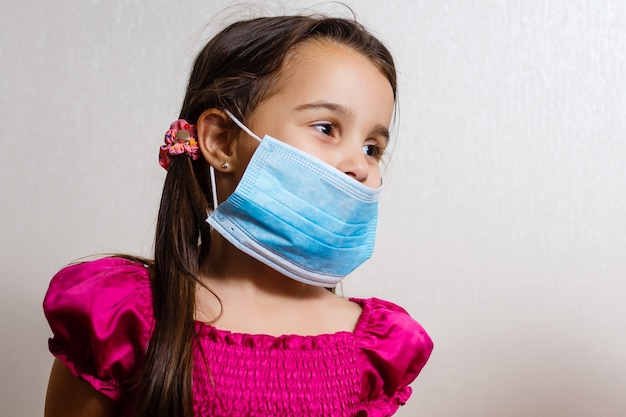 Une petite fille porte un masque médical non permanent.