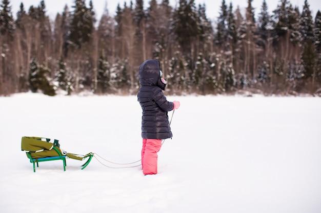 Petite fille porte son traîneau dans la neige