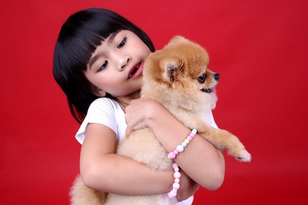 Petite fille porter un chien en studio.