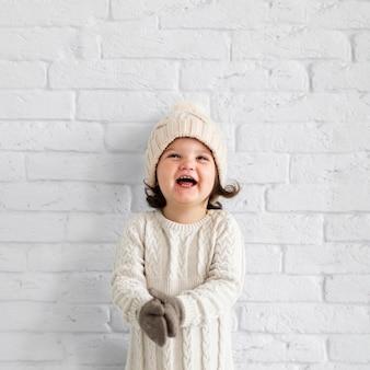 Petite fille posant à côté d'un mur blanc