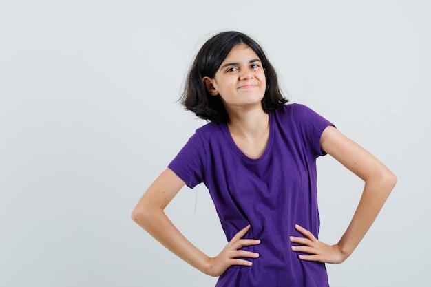 Petite fille posant debout en t-shirt et à la joyeuse