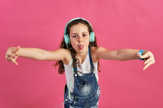 Petite fille posant avec des écouteurs avec sa langue sur un mur rose