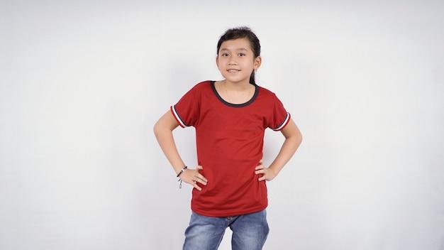 Petite fille posant joyeusement avec les deux mains sur la taille isolé sur fond blanc