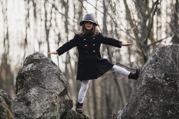 Petite fille posant sur des roches