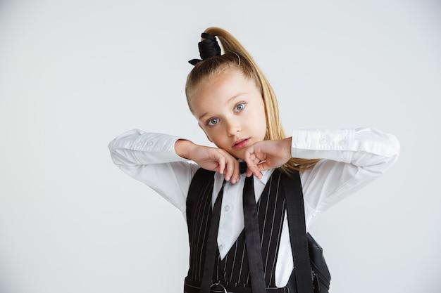 Petite fille posant en uniforme scolaire avec sac à dos sur mur blanc