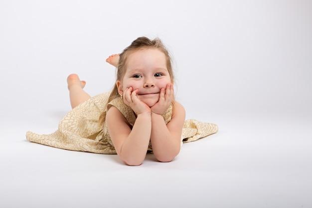 Petite fille pose en belle robe sur fond gris