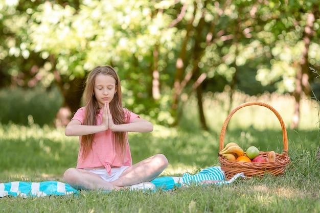 Petite fille en position de yoga dans le parc,