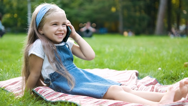 Petite fille positive ayant une conversation sur son téléphone portable dans un parc d'été.