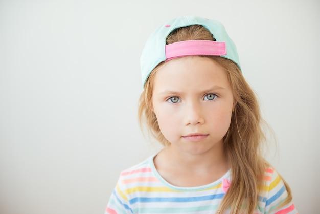 Petite fille positive dans des vêtements à la mode et une casquette