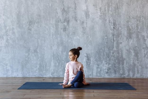 Petite fille pratiquant le yoga assise sur le tapis, s'entraînant dans la salle de sport, sur la scène du mur du loft avec espace libre