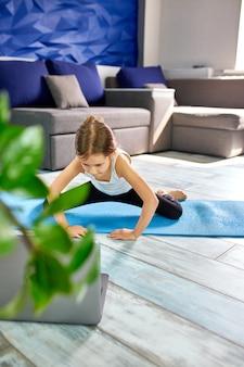 Petite fille pratiquant le yoga, l'étirement, la remise en forme par vidéo sur ordinateur portable