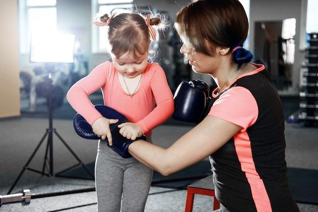 La petite fille pratique la boxe, la petite fille met des gants de boxe à sa mère, sa mère et sa fille se préparent pour la bataille