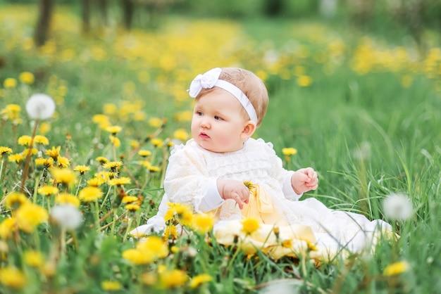 Petite fille sur le pré avec des pissenlits, bébé heureux parmi les pissenlits.