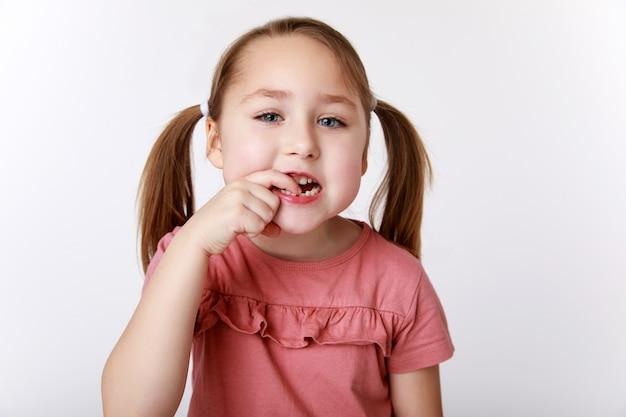 Petite fille avec la première dent de bébé qui se balance
