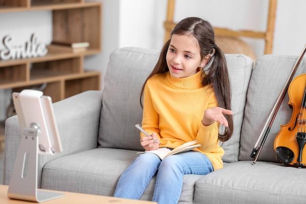 Petite fille prenant des cours de musique en ligne à la maison
