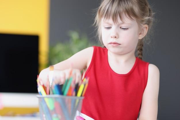 Petite fille prenant un crayon multicolore à partir de cours de dessin de conteneurs pour concept d'enfants