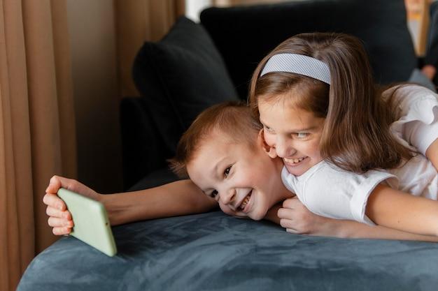 Petite fille prenant un selfie à la maison avec son frère