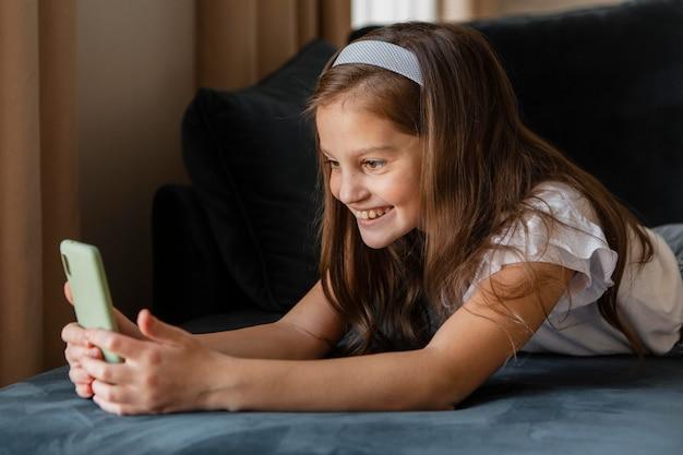 Petite fille prenant un selfie à la maison
