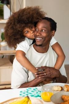 Petite fille prenant son petit déjeuner avec son père